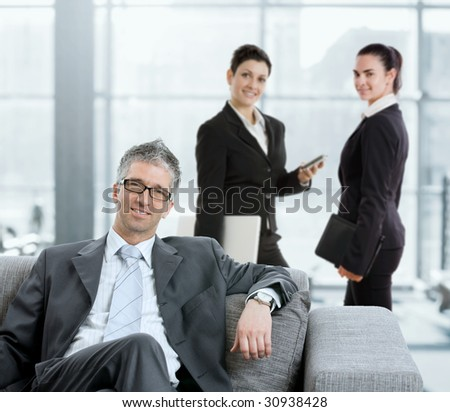 Portrait of businessman sitting on sofa in office lobby. Two businesswomen talking in the background.
