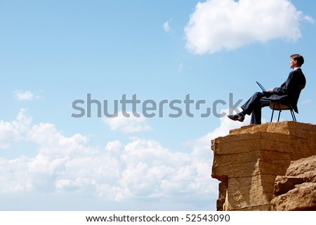 Portrait of businessman sitting on the chair on edge of cliff - stock photo