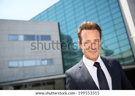 Portrait of businessman standing in front of modern building - stock photo