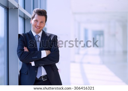 Portrait of businessman standing near window in office . - stock photo