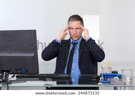 Portrait Of Businessman Suffering From Headache In Office - stock photo