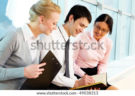 Portrait of businessman surrounded by his colleagues making notes in notepad