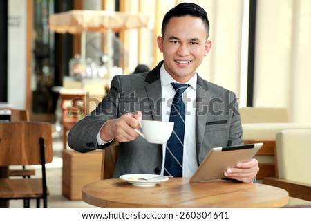 portrait of businessman taking a break at coffee shop - stock photo