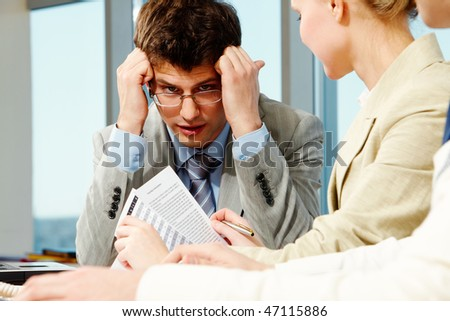 Portrait of businessman touching his head and thinking with colleagues near by