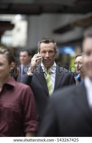 Portrait of businessman using mobile phone amidst coworkers