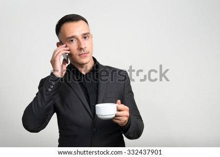 Portrait of businessman using phone and holding coffee cup - stock photo