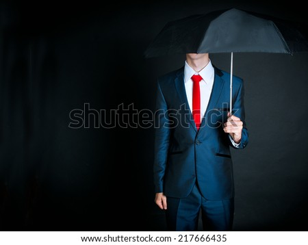 Portrait of businessman wearing dark suit and red tie holding an umbrella - stock photo