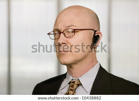 Portrait of businessman with a hands-free phone in his ear - stock photo