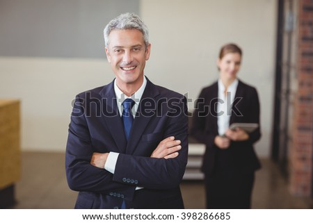 Portrait of businessman with arms crossed while female colleague standing in background - stock photo