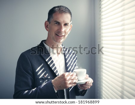 Portrait of businessman with cup of coffee - stock photo