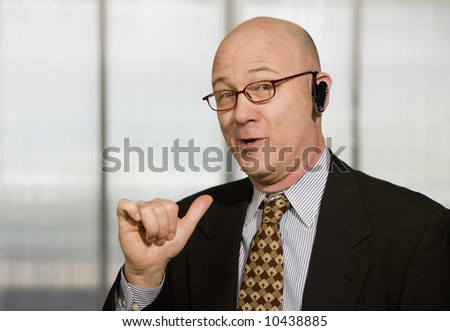 Portrait of businessman with hands-free phone in his ear making a hand gesture - stock photo