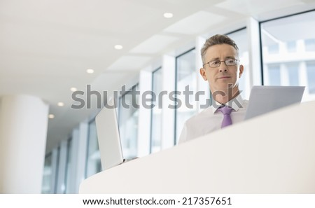 Portrait of businessman with laptop and documents at railing - stock photo