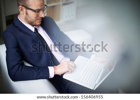 Portrait of businessman with laptop working in office - stock photo