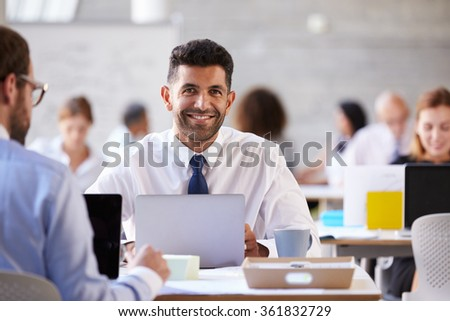 Portrait Of Businessman Working On Laptop In Busy Office - stock photo