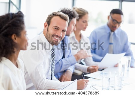 Portrait of businessman writing a report in office