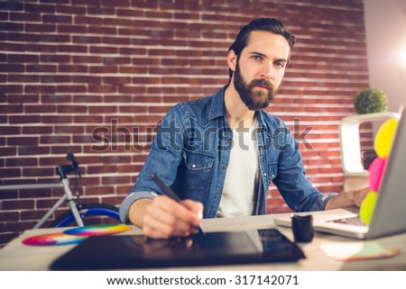 Portrait of businessman writing on graphic tablet while using laptop in creative office - stock photo