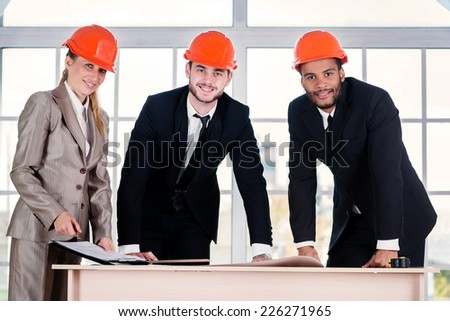 Portrait of businessmen architects. Three businessmen architect met in the office to discuss business projects. Successful young people in the construction helmets are on the table - stock photo