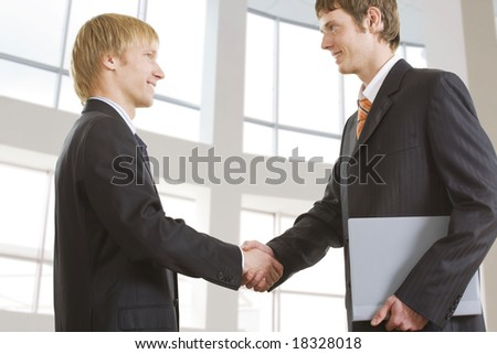 Portrait of businessmen shaking hands at meeting - stock photo