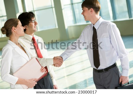 Portrait of businessmen shaking hands at meeting with businesswoman near by - stock photo