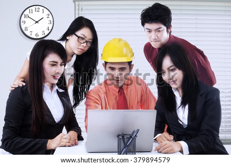 Portrait of businesspeople and male architect discussing together while using laptop computer in the meeting at office - stock photo