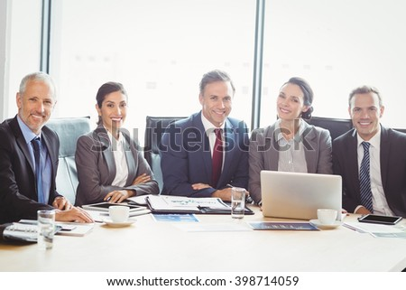 Portrait of businesspeople in conference room during meeting - stock photo
