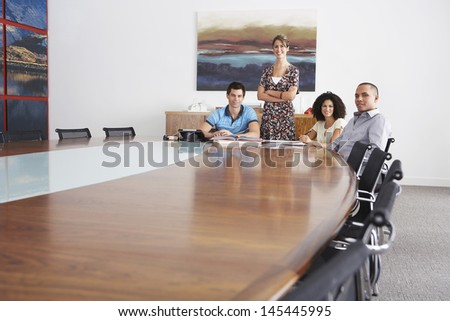 Portrait of businesspeople in meeting at the end of a conference table - stock photo