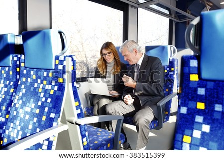Portrait of businesspeople sitting on train and using laptop while working online.