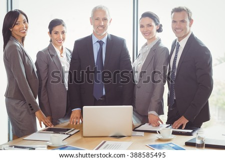 Portrait of businesspeople smiling in conference room - stock photo