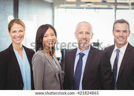 Portrait of businesspeople standing and smiling in office - stock photo