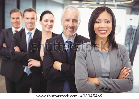 Portrait of businesspeople standing with arms crossed in office - stock photo
