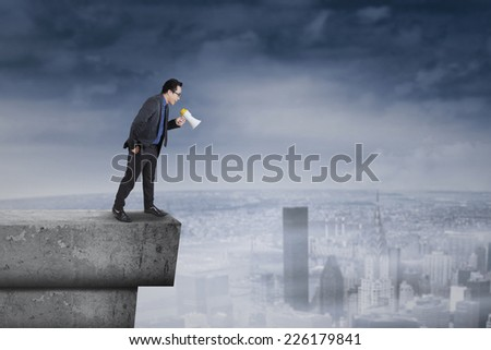 Portrait of businessperson standing on rooftop and screaming to down with a megaphone - stock photo