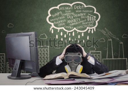 Portrait of businessperson wearing a gas mask facing many problems with doodle on the blackboard - stock photo