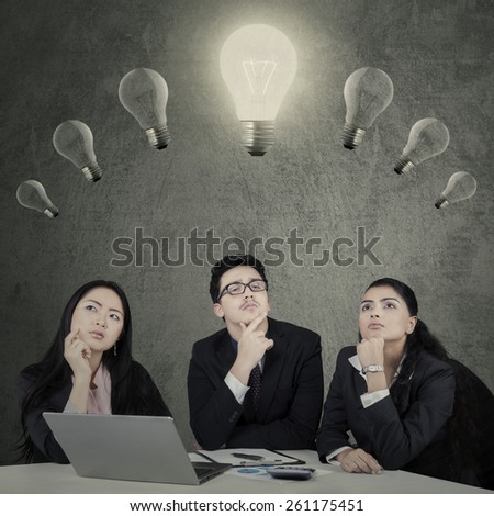 Portrait of businessteam with thinking expression while looking at lightbulb - stock photo