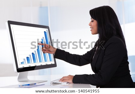 Portrait Of Businesswoman Analyzing Graph On Computer - stock photo