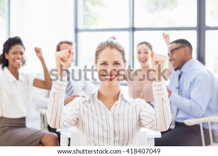 Portrait of businesswoman celebrating success in office with her colleagues - stock photo