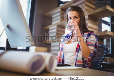 Portrait of businesswoman drinking water at computer desk in creative office - stock photo