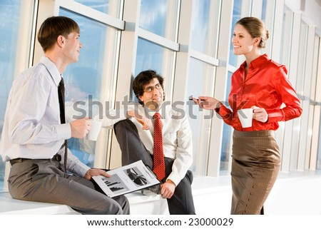 Portrait of businesswoman holding cup and explaining new project to businessmen - stock photo