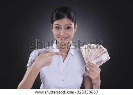 Portrait of businesswoman holding currency - stock photo