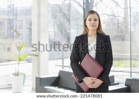 Portrait of businesswoman holding file while standing at office lobby - stock photo