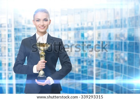 Portrait of businesswoman keeping gold cup, blue background. Concept of victory and success - stock photo