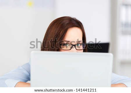 Portrait of businesswoman looking over at the computer monitor - stock photo
