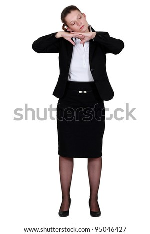 portrait of businesswoman pretending to sleep with face resting on hands - stock photo