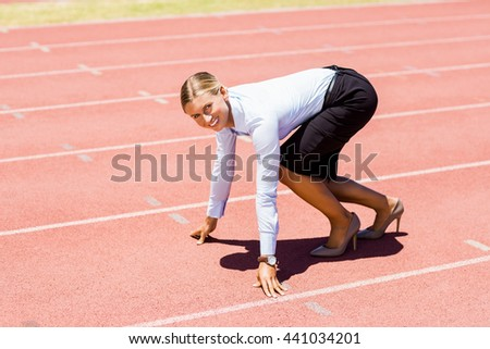 Portrait of businesswoman ready to run on running track on a sunny day