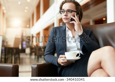 Portrait of businesswoman sitting at coffee shop using mobile phone. Female executive with cup of coffee talking on cell phone. - stock photo