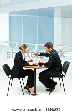 Portrait of businesswoman sitting at the table and typing something on laptop looking at screen with businessman pointing at the monitor with pen - stock photo