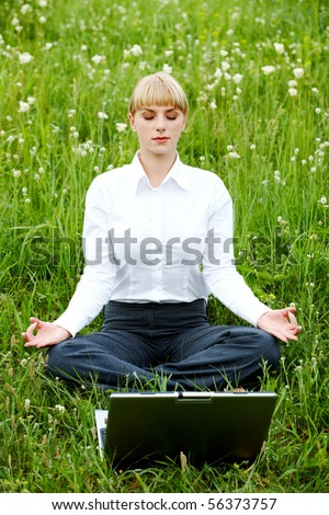 Portrait of businesswoman sitting on the grass and meditating - stock photo
