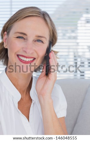 Portrait of businesswoman talking on phone in bright office