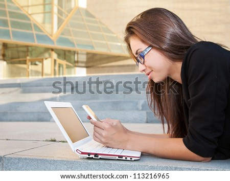 Portrait of businesswoman texting near office building
