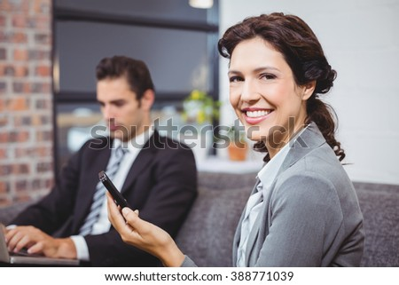 Portrait of businesswoman using cellphone while colleague working in background