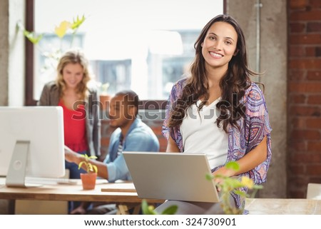 Portrait of businesswoman using laptop while colleague seen in background at creative office - stock photo